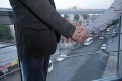 Handshake of two businessmen dressed in a jacket and shirt against the background of a panoramic window, on a high floor, overlook royalty free stock photos