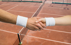 Handshake between two tennis player in a competition. Two tennis player take a handshake with a court tennis in background Royalty Free Stock Image