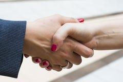 Handshake of two women Stock Photo
