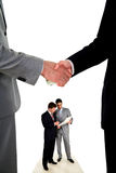 Handshake and two working businessmen Royalty Free Stock Photos