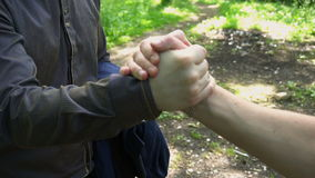 Handshake of two young men in the woods stock footage