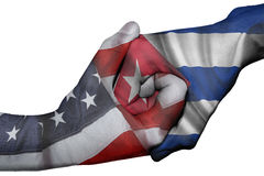 Handshake between United States and Cuba. Diplomatic handshake between countries: flags of United States and Cuba overprinted the two hands Royalty Free Stock Images