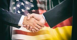 Handshake on USA - Germany flags background stock photo