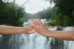 Handshake at waterfall Stock Photos
