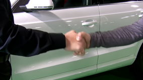 Handshake. White car deal. Close up of two men or man and woman shaking hands in front of shiny brand new white car stock video footage