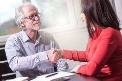 Handshake between woman and man at office, light effect stock image