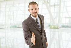 Handshake. Young businessman in suit offering to shake the hand at the office Royalty Free Stock Images