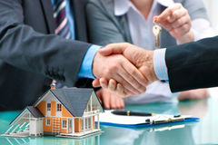 Handshakes with customer after contract signature. Estate agent shaking hands with customer after contract signature stock photography