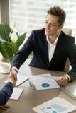 Handshaking бизнесмена на встрече, документе удерживания, делая dea Стоковые Фотографии RF