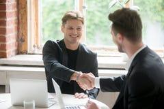 Handshaking 2 бизнесменов на обсуждая встрече в острословии офиса Стоковые Фотографии RF