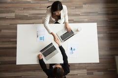 Handshaking коммерсанток над столом офиса делая успешный de Стоковые Изображения