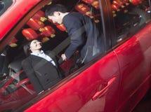 Handshaking сотрудников рядом с автомобилем на ноче, красными фонариками на предпосылке Стоковое Изображение