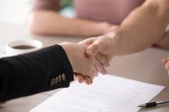 Handshaking человека и женщины после подписания документов, успешного de Стоковое фото RF