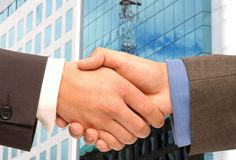 Handshaking. Two business men shaking hands in front of an office building Stock Image