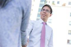 Handshaking biznesowy azjatykci mężczyzna i kobiety plenerowi z buildin zdjęcie royalty free