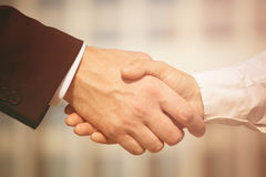 Handshaking. Business handshake on bright background. Photo of handshake of business partners after signing promising contract. Toned image Royalty Free Stock Photos
