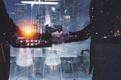 Handshaking business person in office. concept of teamwork and partnership. double exposure. Handshaking business person in the office. concept of teamwork and royalty free stock image