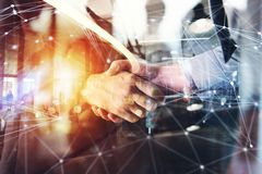 Handshaking business person in the office. concept of teamwork and partnership. double exposure. Agreement between business people with light effects royalty free stock photography