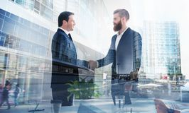 Handshaking business person in office. concept of teamwork and partnership. double exposure stock image