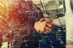 Handshaking business person in office with network effect. concept of teamwork and partnership. double exposure royalty free stock image