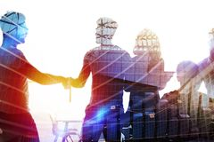 Silhouette of young workers shaking hands in the office. concept of teamwork and partnership. double exposure stock photo