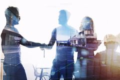 Silhouette of young workers shaking hands in the office. concept of teamwork and partnership. double exposure royalty free stock images
