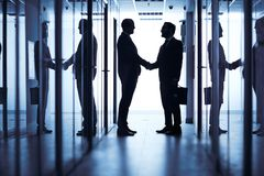 Handshaking in corridor Stock Photo
