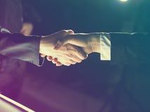 Handshaking della stretta di mano su chiaro e su oscurità Immagine Stock