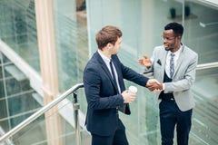 Handshaking för två blandras- affärsmän i det moderna kontoret för slut av det stora avtalet arkivfoto