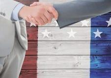 Handshaking för två män mot en träbakgrund med amerikanska flaggan Royaltyfria Foton