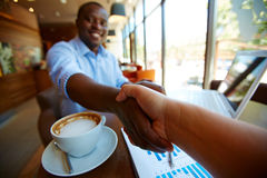Handshaking. Image of cup of latte and business document and handshaking of business partners in cafe Stock Photos