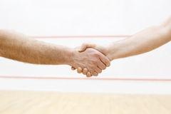 Handshaking before match. In squash. Two men are going to have sport battle. Photo with selective focus. Squash players shaking hand before match in court Stock Images