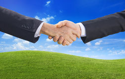 Handshaking and Mountain with Sky in Background Royalty Free Stock Photo