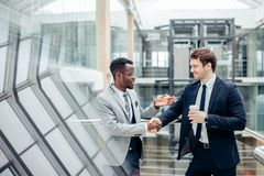Handshaking 2 multiracial бизнесменов в современном офисе для конца большого дела стоковое фото