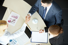 Handshaking partners. Image of business partners handshaking after signing contract Royalty Free Stock Image
