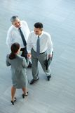 Handshaking partners. Image of business partners handshaking after signing contract Stock Photos
