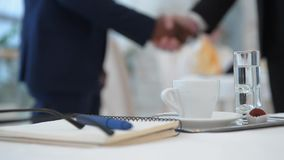 Handshaking of two businessmen. Closeup portrait of cup of coffee represented on table in restaurant while two businessmen shaking hands stock video