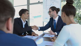 Handshaking of two businessmen during a successful deal. Two businessmen are sitting in the office at the conference. Two business people are making a successful stock footage