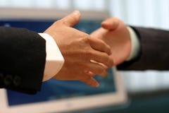 Handskaka på kontoret Arkivfoto