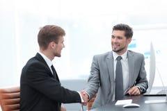 Handskakning av affärspartners som sitter på ett skrivbord Royaltyfri Bild