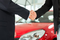Handskakning av två män i dräkter med en röd bil Royaltyfri Fotografi