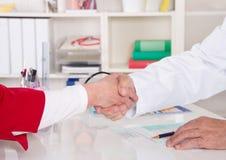 Handskakning: doktorn säger välkomnande till hans höga patient Royaltyfri Fotografi
