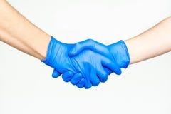 Handskakning med blåa medicinska handskar arkivbild