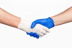 Handskakning med blåa och vita medicinska handskar royaltyfri foto