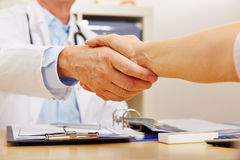 Handskakning med doktorn och patienten Arkivbild