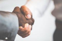 Handskakning mellan afrikanskt och en caucasian man royaltyfri fotografi