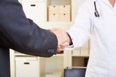 Handskakning mellan doktorn Arkivfoto