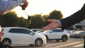 Handskakning mellan två utomhus- affärsmän Manhänder i skjortan som ger tangenter av bilen till hans vän Arm av affärsmannen lager videofilmer