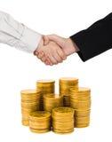 Handskakning och guld- mynt Arkivfoto