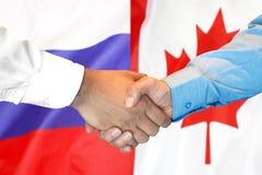 Handskakning på Kanada och Ryssland flaggabakgrund royaltyfri bild